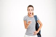 Mulher surpreendida com a trouxa que guarda o smartphone e que olha a câmera Foto de Stock