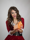 Mulher surpreendida de Santa que abre o presente de Natal dourado pequeno Fotografia de Stock