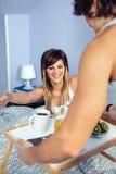 Mulher surpreendida na cama que olha para tomar o café da manhã servido Imagem de Stock