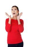 Mulher surpreendida nova que olha acima Imagens de Stock