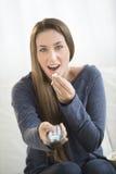 Mulher surpreendida que come a pipoca ao olhar a tevê Imagem de Stock Royalty Free