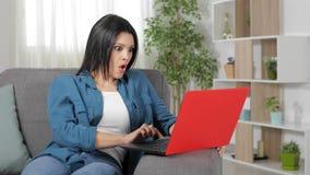 Mulher surpreendida que encontra o índice no portátil em casa vídeos de arquivo