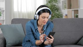 Mulher surpreendida que escuta a música em um sofá filme