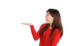 Mulher surpreendida que guarda o produto Imagens de Stock