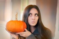 Mulher surpreendida que guarda uma abóbora Foto de Stock Royalty Free