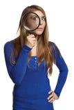 Mulher surpreendida que olha através da lupa em você Fotografia de Stock Royalty Free
