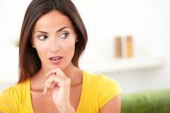 Mulher surpreendida que olha ausente ao contemplar fotografia de stock