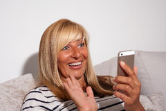 Mulher surpreendida que olha seu telefone Imagem de Stock Royalty Free