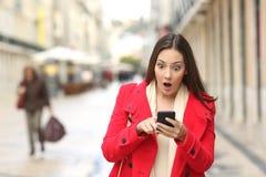 Mulher surpreendida que verifica o telefone esperto na rua fotos de stock