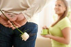 Mulher surprising do homem com flor Fotografia de Stock Royalty Free