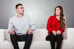 Mulher tímida e homem que sentam-se no sofá Primeira data imagens de stock