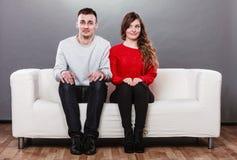 Mulher tímida e homem que sentam-se no sofá Primeira data foto de stock royalty free
