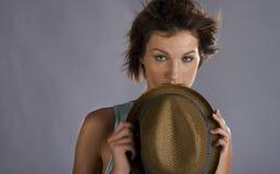 Mulher tímida que esconde atrás de seu chapéu imagem de stock
