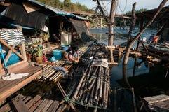 A mulher tailandesa lava-a roupa em um rio de madeira da jangada Imagem de Stock