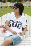 Mulher tailandesa que senta-se em um banco Fotografia de Stock Royalty Free