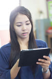 Mulher tailandesa que usa a tabuleta Fotografia de Stock