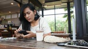 A mulher tailandesa senta-se relaxa o smartphone do jogo e para beber o chocolate do frappe na cafetaria vídeos de arquivo