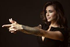 A mulher tattooed com cabelo ondulado de brilho exuberante e perfeitos bonitos compõem o fingimento apontar algo com gesto do tir Foto de Stock