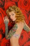 Mulher tattooed de encantamento no fundo com flores Fotografia de Stock