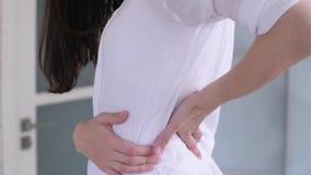 A mulher tem a dor lombar vídeos de arquivo