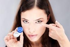 A mulher tem a lente de contato em seu dedo imagem de stock