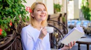 A mulher tem o terraço do café da bebida fora Oportunidade do achado de ler mais Combinação do café da caneca e do livro interess fotografia de stock
