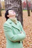 A mulher tem um descanso no parque do outono Imagem de Stock