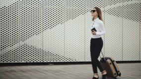 A mulher tem uma chamada com sua bagagem no aeroporto video estoque