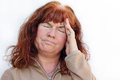 A mulher tem uma dor de cabeça Foto de Stock