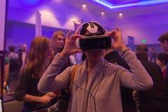 A mulher tenta auriculares da engrenagem VR de Samsung da realidade virtual Imagens de Stock