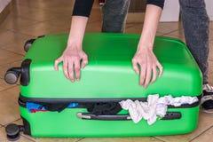 A mulher tenta fechar a mala de viagem enchida em demasia imagem de stock