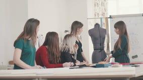 A mulher tenta sobre o vestido em um manequim Desenhador de moda fêmea no trabalho vídeos de arquivo