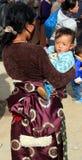 Mulher tibetana que leva sua criança Imagem de Stock Royalty Free