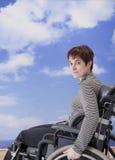 Mulher tida desvantagens na cadeira de rodas na praia Foto de Stock Royalty Free