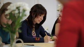 A mulher tira o assento na tabela no grupo que aprende a pintura, ainda vida com vaso e flores vídeos de arquivo