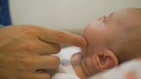 A mulher toca playfully no mordente de uma criança pequena que encontra-se em uma ucha filme