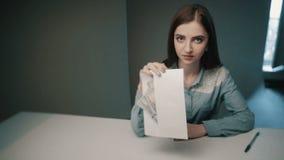 A mulher toma cinco cem dinheiros do dinheiro do envelope no fundo cinzento O oficial obteve o subôrno filme