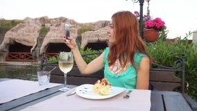 A mulher toma imagens dsi mesma em seu smartphone no restaurante vídeos de arquivo