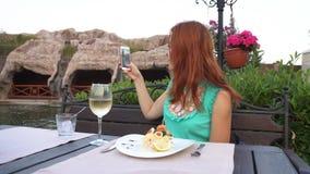 A mulher toma imagens dsi mesma em seu smartphone no restaurante filme