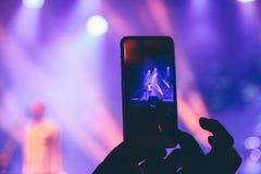 A mulher toma imagens no telefone em um concerto foto de stock royalty free
