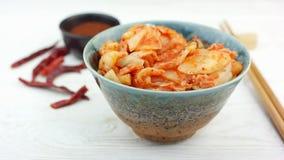A mulher toma o aperitivo coreano tradicional Kimchi da bacia com hashis, movimento lento video estoque