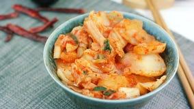 A mulher toma o aperitivo coreano tradicional Kimchi da couve da bacia com hashis vídeos de arquivo