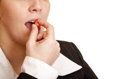 A mulher toma o comprimido de dor de encontro à dor de cabeça Imagens de Stock