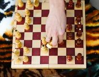 A mulher toma partes de xadrez de um quadro-negro Imagens de Stock Royalty Free