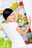 A mulher toma a pimenta de sino do refrigerador aberto Fotografia de Stock