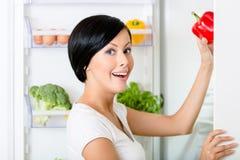 A mulher toma a pimenta vermelha do refrigerador aberto Imagens de Stock Royalty Free