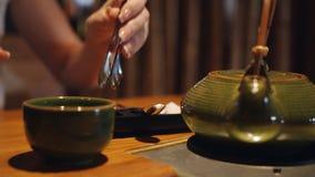 A mulher toma tenazes de brasa especiais adoça cubos e põe-nos em um copo do chá no restaurante video estoque
