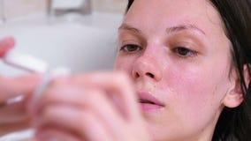A mulher toma um creme do frasco que encontra-se no banheiro Enfrente o close-up