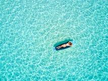 A mulher toma um sunbath em uma prancha sobre as águas tropicais de Maldivas fotos de stock