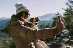 A mulher toma uma imagem com seu cão na montanha imagens de stock royalty free